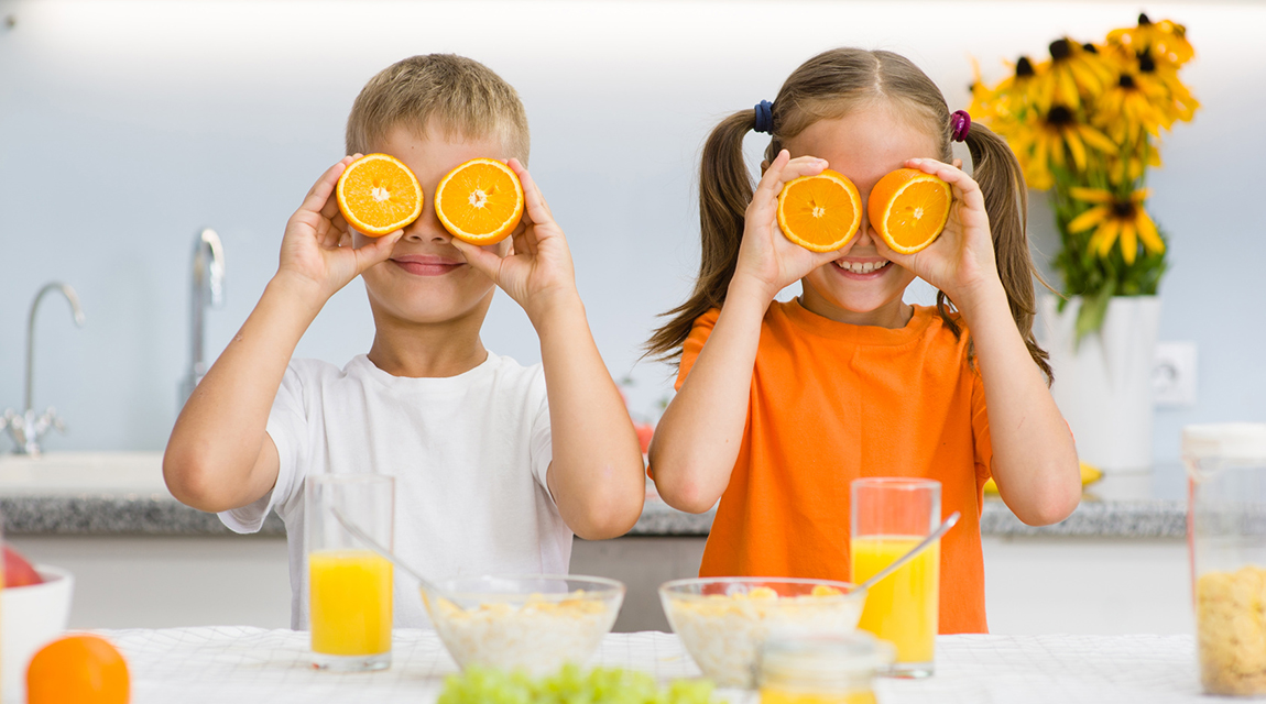 Happy kids holds orange before his eyes like in glasses.